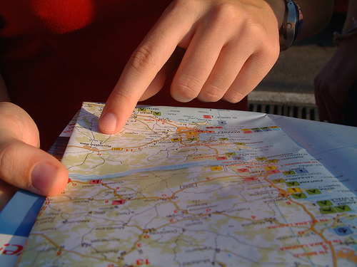 Finger pointing at road map