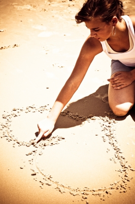 woman drawing heart in sand